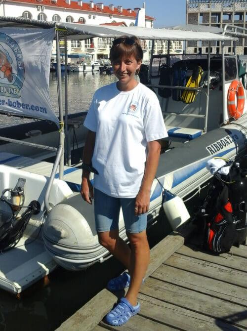 Инструктор по дайвингу Виктория Лесина стоит у лодки