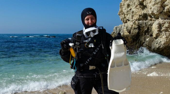 Мастер-Инструктор Виктория Лесина в полном снаряжении стоит на берегу моря
