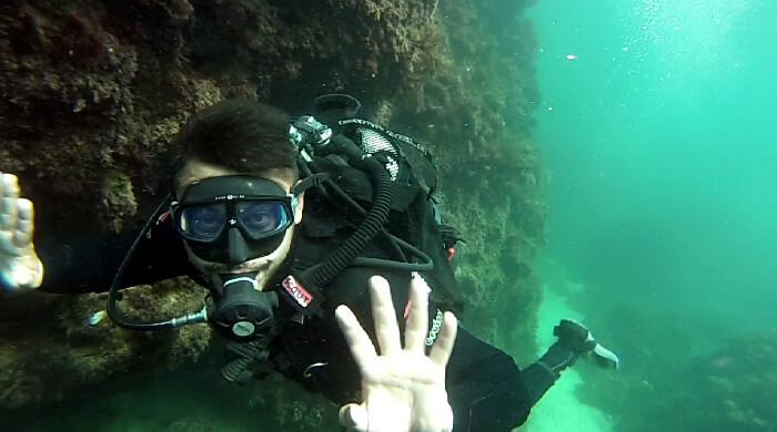 Парень под водой приветственно машет рукой