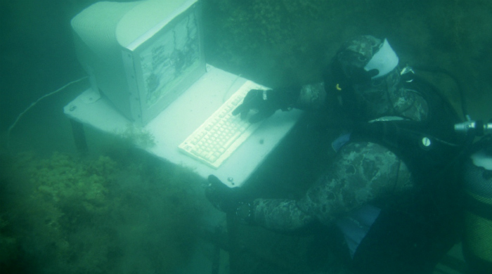 Фото дайвера, сидящего за компьютером под водой