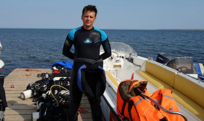 Инструктор по дайвингу Денис Шиян стоит у лодки