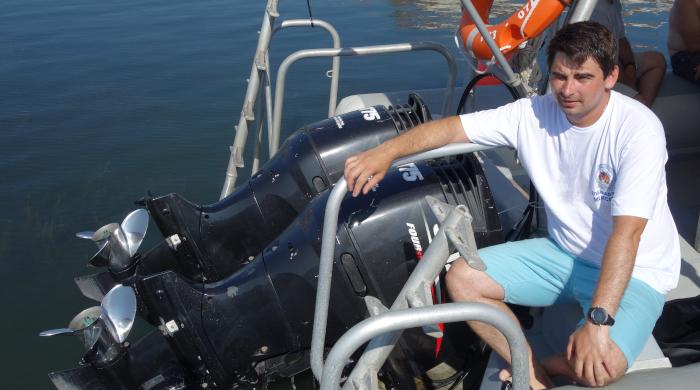 Instructor NDL Rank 2 Максим Пьянков около лодочных моторов. Фото
