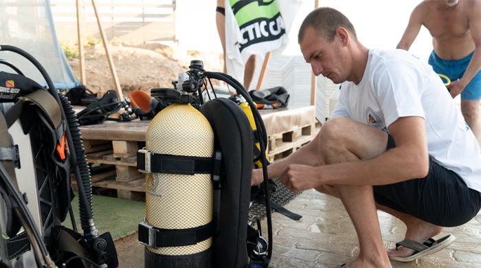 Дайвмастер Олег Соловьев собирает оборудование. Фото